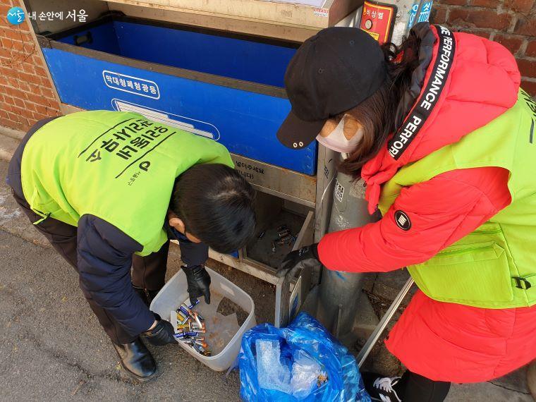 폐건전지통에서 건전지가 아닌 쓰레기를 꺼내고 있다.