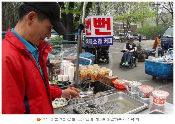 손님이 물건을 살 때 그냥 집어 먹어보라 말하는 김수복 씨