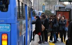 시내 버스에 승객들이 탑승하고 있다