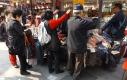 남대문시장 옷가게에서 사람들이 옷을 고르고 있다