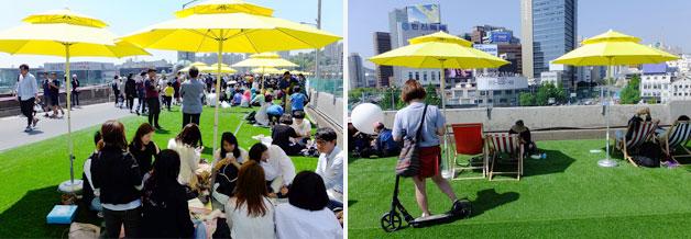 잔디밭 위 파라솔 밑 돗자리와 썬배드에서 쉬어가는 시민들