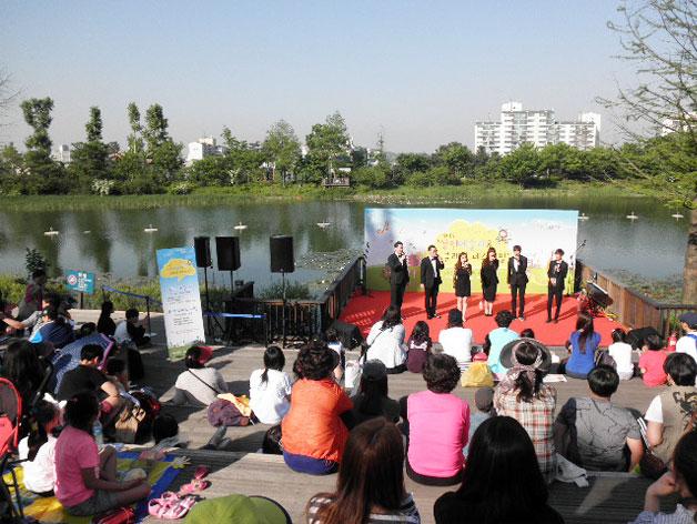 호수를 배경으로 양천예술제 공연이 한창이다. 데크에 앉아 관람하는 시민들