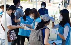 13일 오전 서울 강서구의 한 중학교에서 열린 2015년도 서울시 공무원임용시험 필기시험에 응시한 수험생들이 보건소 직원들에게 발열 체크와 손소독을 받고 있다.ⓒ뉴시스