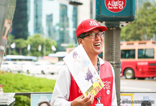 지하철역 입구에서 빨간 조끼를 입고 빅이슈 잡지를 판매하는 판매원 ⓒ빅이슈코리아(이경민)