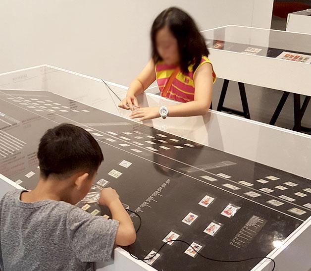 아이들이 북한 우표를 주의 깊게 관찰하고 있다