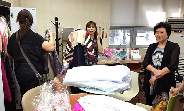 대여할 한복을 직접 펼쳐보며 고르고 있는 고객들