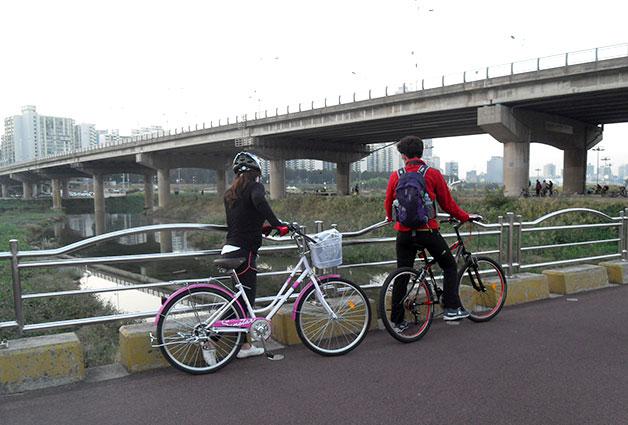 도림천과 안양천 합수부에 자전거를 댄 대학생 남녀