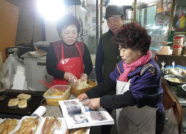 신곡재래시장에서 마을 사진첩을 보는 주민들