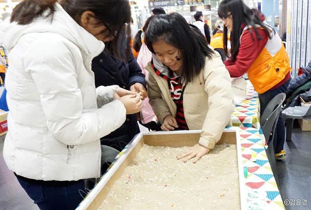 한 어린이가 모래 속에서 알파벳 구슬을 찾고 있다ⓒ김윤경