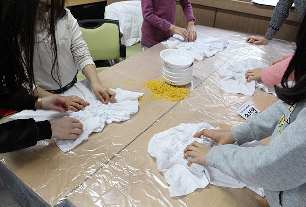 아이들이 작은 손으로 티셔츠 주름을 잡는 모습