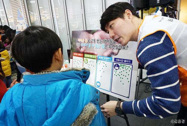 월드비전 직원이 한 어린이에게 물부족을 위해 할 수 있는 일을 설명하고 있다ⓒ김윤경