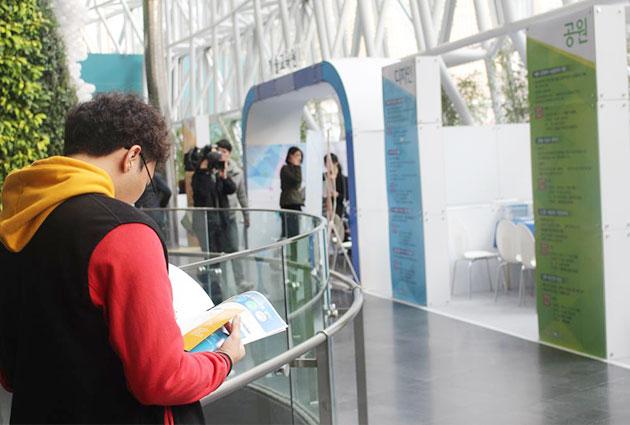박람회에 참여한 한 청년이 안내책자를 살펴보고 있다