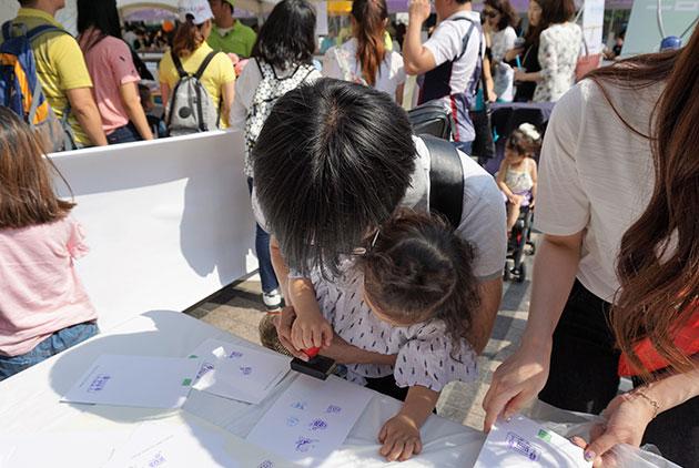 아빠와 아이가 함께 행사 스탬프를 찍고 있다