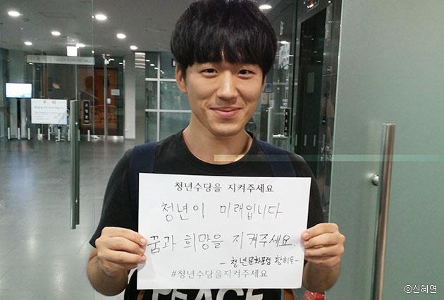 `청년수당 그것이 알고싶다` 행사에 참여한 황희두(25)씨가 청년수당에 대한 바람을 적은 피켓을 들고 있다. ⓒ신혜연