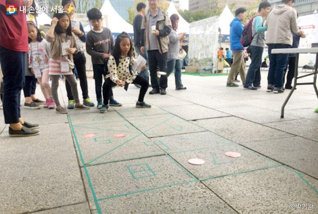 어린이들이 `GMO OUT`이라는 딱지를 던지며 땅따먹기 놀이를 즐기고 있다. ⓒ 박기완