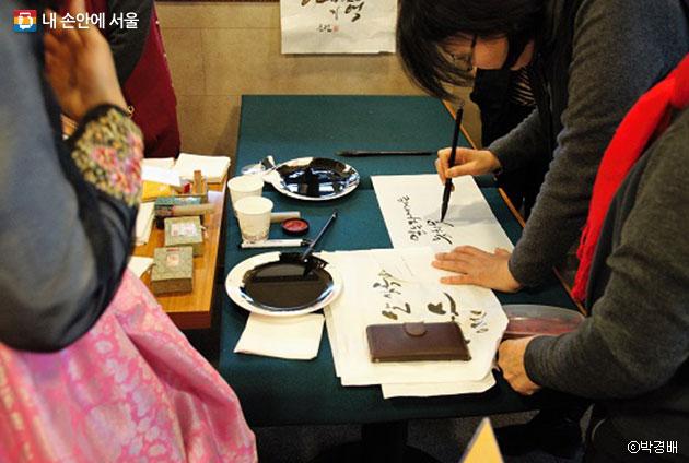참가자가 써온 좌우명으로 캘리그라피를 쓰고 있는 작가. ⓒ박경배