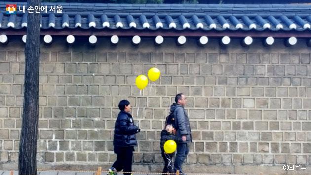 노란 풍선을 손에 쥐고 광화문으로 걸어가는 가족 ⓒ최은주