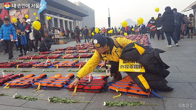세월호 희생자를 상징하는 304개의 구명조끼 중 아들의 이름이 적힌 조끼를 쓰다듬고 있는 유가족. ⓒ최은주