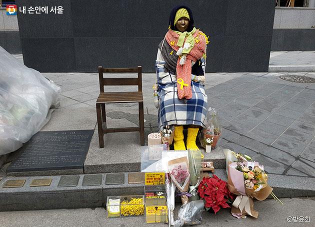 평화의 소녀상 발밑에 시민들이 갖다 놓은 꽃다발과 선물들 ⓒ방윤희