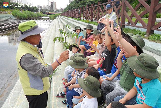 응암노인복지관의 수생태해설사가 아이들에게 생태교육을 진행하고 있다