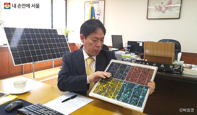 """박진섭 서울에너지공사 사장은 """"신재생에너지 시장이 활성화하기 위해서는 디자인도 중요한 요소""""라며 색깔을 입힌 태양광 모듈을 보여주고 있다. ⓒ 박희영"""