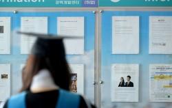 한 대학교에서 학사모를 쓴 졸업생이 취업 게시판을 보고 있다.ⓒ뉴시스