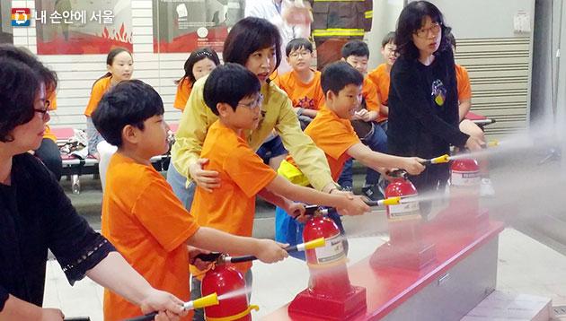 어린이들이 화재안전 교육 프로그램에서 소화기 사용법을 체험하고 있다