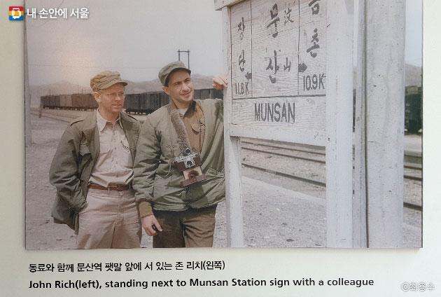 동료와 함께 문산역 팻말 앞에 서 있는 존 리치(왼쪽인물) ⓒ최용수