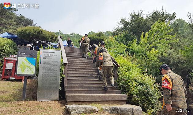강서둘레길 인근에 설치된 `호국충혼위령비` 안내판을 지나는 노병들 모습 ⓒ최용수