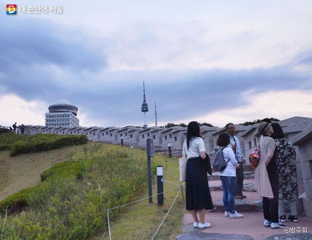 서울 순성길에서 서울 시내를 내려다보며 한양도성의 탄생과정을 듣고 있다. ⓒ방주희