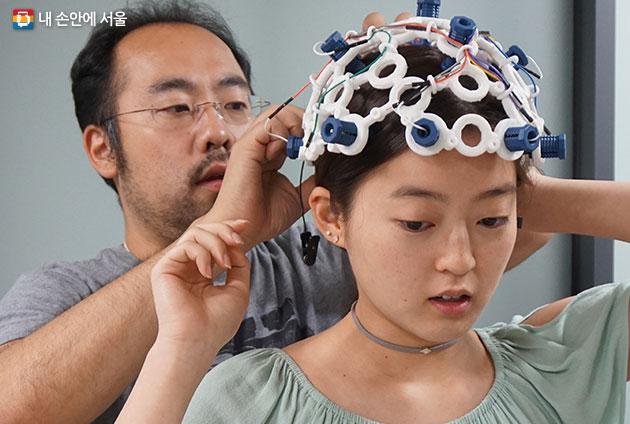 `뇌파산책` 참여자는 뉴욕 바이오 메디컬(OpenBCI)에서 제공한 EEG 헤드셋을 사용해 자신의 상태를 측정하게 된다. 헤드셋 착용을 돕고 있는 하세가와 토루 교수