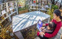 정원박람회에서 책을 읽는 엄마와 아이