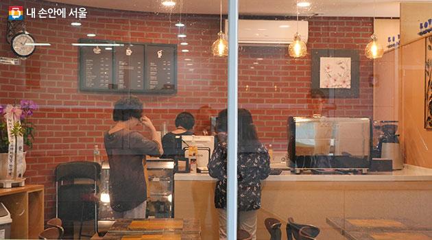 유리창 밖에서 바라본 본카페 실내모습. 주민들이 메뉴판 앞에 서서 주문을 하고 있다.