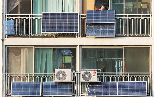 서울 노원구의 한 아파트 단지에서 한 입주민이 베란다에 설치된 태양광 판넬을 살펴보고 있다.ⓒnews1