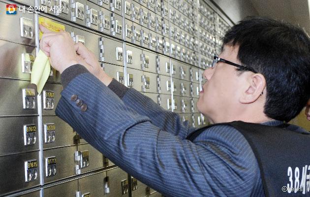서울시 38세금징수과 직원이 고액세금 체납자에 대한 대여금고 봉인 작업을 하고 있다.ⓒnews1