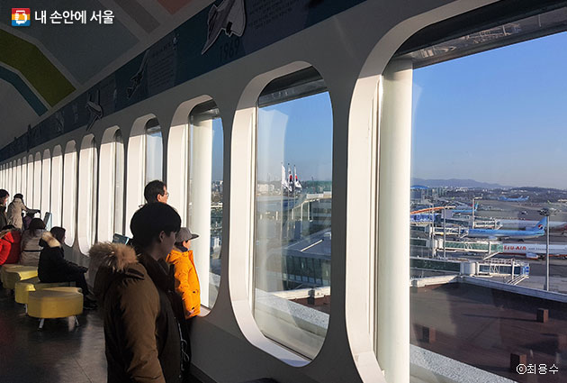 시민들이 창가에서 비행기와 공항의 모습을 관람하고 있다. ⓒ최용수