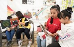`제7회 마포 동네 책 축제`에서 자원봉사자들이 아이들에게 책을 읽어주고 있다 ⓒnews1
