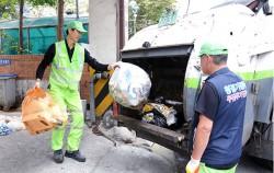 환경미화원이 쌓인 쓰레기를 치우고 있다