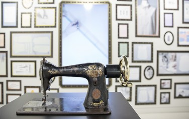 손때 묻은 낡은 재봉틀, 재봉틀을 돌릴 때마다 옷 만드는 과정을 담은 영상을 볼 수 있다.