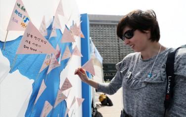 남북정상회담을 하루 앞둔 26일 서울광장을 찾은 한 외국인이 남북정상회담 성공 개최를 위한 소원쓰기 행사에 참여하고 있다