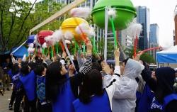 서울광장에서 열린 '지구의 날' 기념식에서 에너지수호천사단 학생들이 모여 박을 털고 있다.