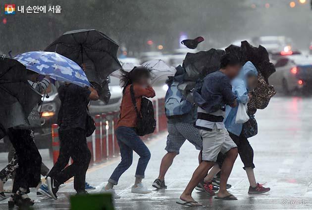 태풍에 맞서 힘겹게 걸어가는 사람들