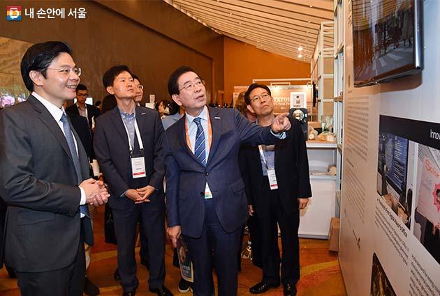 박원순 서울시장이 서울시 홍보부스에서 로렌스 웡 싱가포르 국가개발부 장관(맨 왼쪽)에게 서울로7017을 소개하고 있다