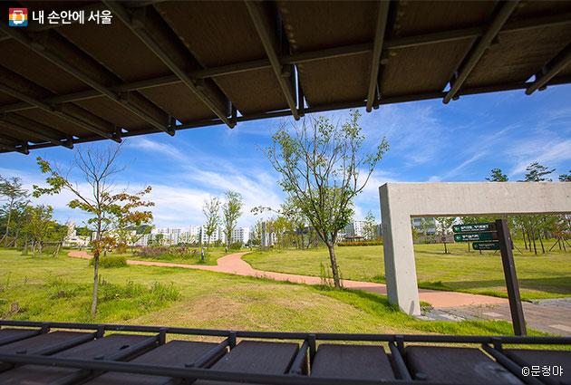 벽돌과 철제로 만든 구조물 사이 구멍으로 촬영해본 공원 풍경