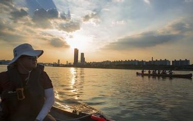 여의도 쪽으로 붉게 물드는 석양을 바라 보며 카누를 타는 시민들