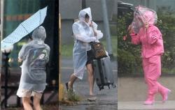 태풍 '솔릭'이 제주를 강타한 23일 강한 비바람이 몰아치는 가운데 사람들이 위태롭게 걸어가고 있다