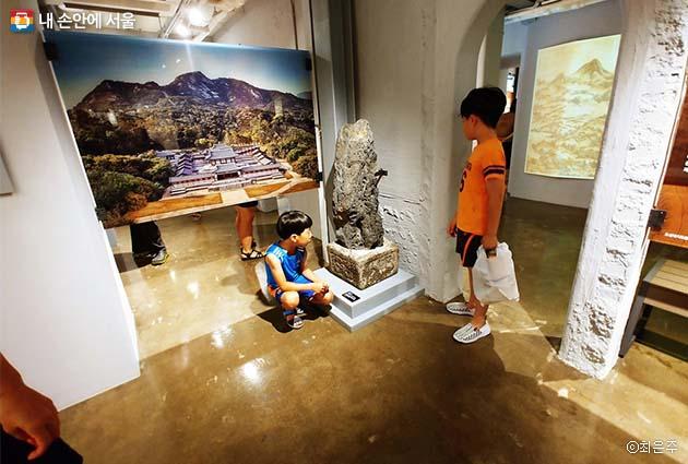 돈의문전시관에 있는 괴석을 들여다보고 있는 어린이들