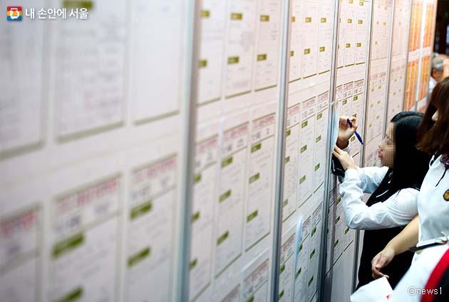 채용박람회에서 채용정보 게시판을 살펴보는 고등학생