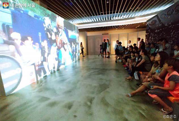탐방객들이 서울과 서울올림픽에 대한 영상을 보고 있다