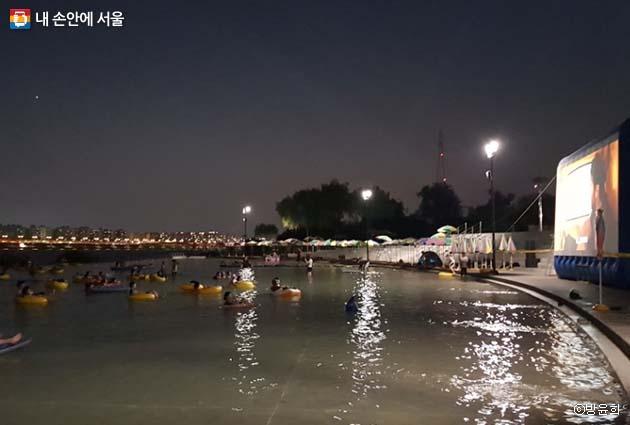 스크린의 불빛이 물속에 스며들어 한여름 밤을 환하게 수놓았다